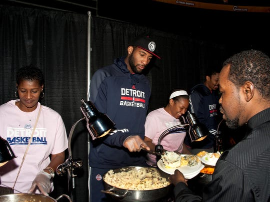 Pistons center Andre Drummond serves mashed potatoes during a Thanksgiving dinner to benefit 700 people from families in Oakland and Wayne counties Tuesday at the Palace.