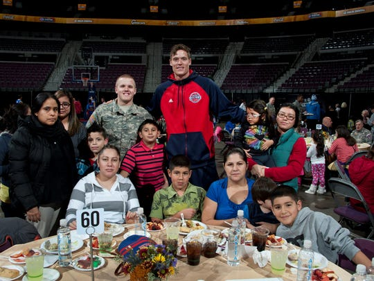 Pistons forward Jonas Jerebko and a member of the U.S. Army take a break for a photo during a Thanksgiving dinner for families from Oakland and Wayne counties Tuesday at the Palace.