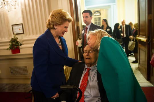Retiring Congressman John Dingell gets a hug from his wife Debbie Dingell, stunning, while greeting Michigan Senator Debbie Stabenow, left, at a reception on Capitol Hill on Dec. 10, 2014.