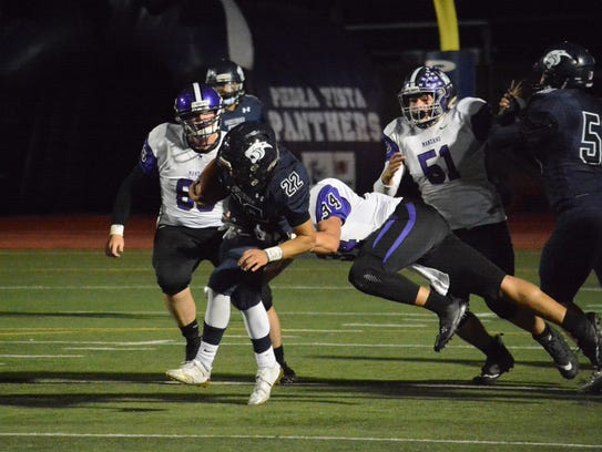 Piedra Vista's McKay Cook breaks a tackle and muscles