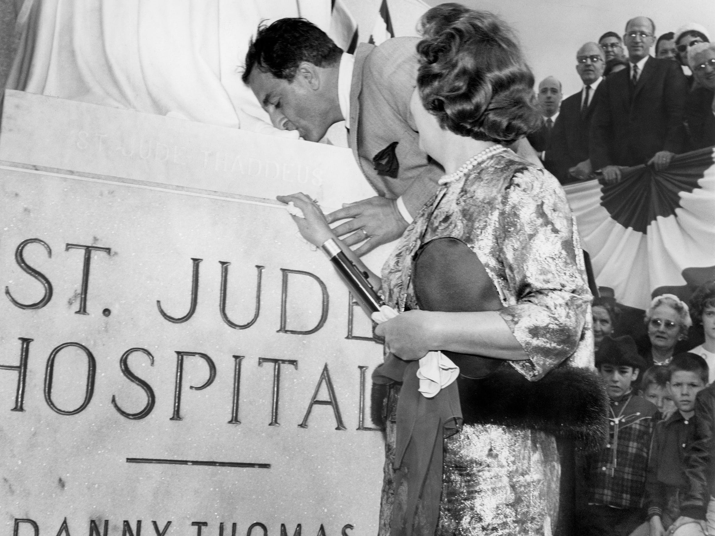 "Danny Thomas kisses the toe of St. Jude Thaddeus as Mrs. Thomas looks on during the formal opening of St. Jude Children's Research Hospital February 4, 1962.  ""This is the greatest day of my life,"" the television performer observed. ""If I should die this minute, I would know why I was born."" Some 9,000 people turned out for the opening."