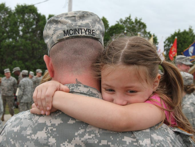 Specialist Matthew McIntyre, with his daughter Eili, 6, Toms River  before ceremony  saluting the troops of the 1st-150th Assault Helicopter Battalion at the National Guard Training Center in Sea Girt.  The Battalion is being deployed to Kosovo for a year.  Sunday July 20, 2014, Sea Girt, NJ. Photo by Robert Ward
