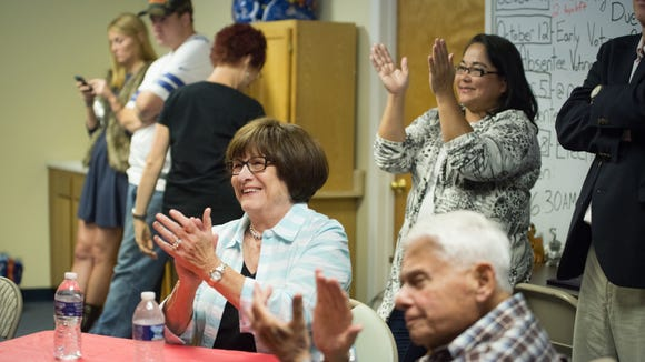 Betty Dubin, center, and her husband, Malcolm, applaud