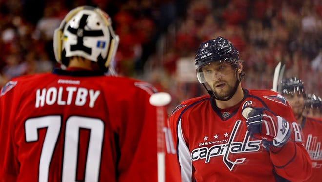 Washington Capitals left wing Alex Ovechkin (8) celebrates with Capitals goalie Braden Holtby (70) after scoring a goal against the New Jersey Devils in the third period at Verizon Center.