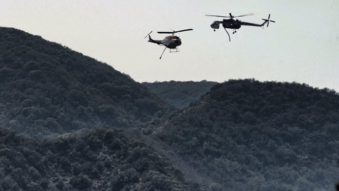 Helicopters make water drops Thursday at the Rey Fire.