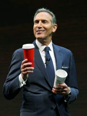 Starbucks CEO Howard Schultz holds one of the company's