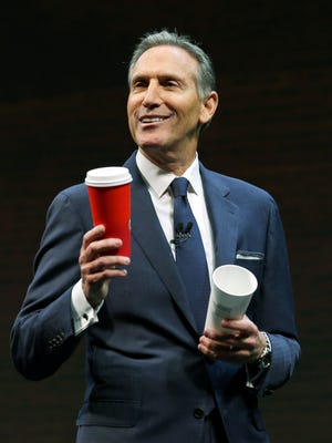 Starbucks CEO Howard Schultz holds one of the company's red holiday cups as he speaks Wednesday, March 23, 2016, at the coffee company's annual shareholders meeting in Seattle.