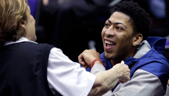 New Orleans Pelicans forward and former Kentucky star Anthony Davis laughs with an usher in the first half of an NCAA college basketball game between LSU and Kentucky in Baton Rouge, La., Tuesday, Feb. 10, 2015. (AP Photo/Gerald Herbert)
