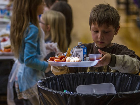 A student at East Elementary in Cedar City throws his food tray in the garbage following lunch. The meals offered during the summer are similar to those served during the school year.