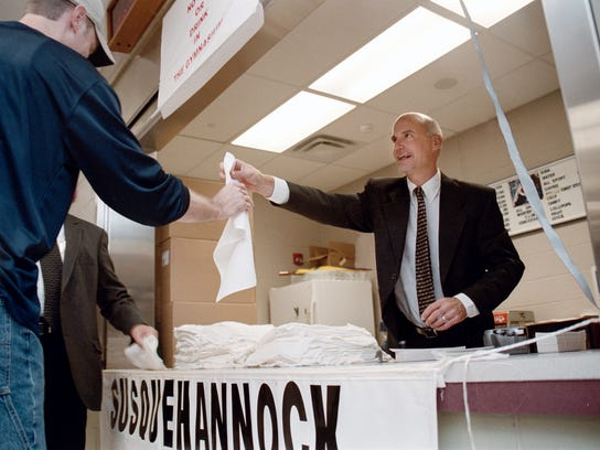 Chuck Abbott, Susquehannock High Schoolís Athletic Director, hands out towels and bumper stickers to those who visited the schoolís open house on Sunday afternoon. Lori Crouse Klauber/York Daily Record. 092803.
