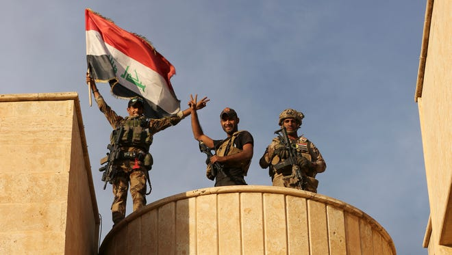 Iraqi special forces forces raise an Iraqi flag after retaking Bartella, outside Mosul, Iraq, on Friday.