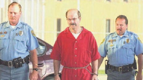 Convicted serial killer Dennis Rader walks into the El Dorado Correctional Facility with two Sedgwick County sheriff's officers on Aug. 19, 2005, in El Dorado, Kansas. Rader, the self-styled BTK killer, admitted to killing 10 people over 30 years and was sentenced to 10 consecutive life terms.