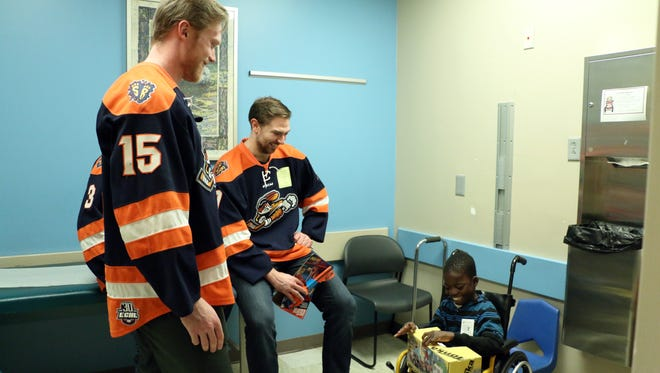 Members of the Greenville Swamp Rabbits watch a patient from the Greenville Shriners Hospital for Children open a Christmas gift the team brought him.