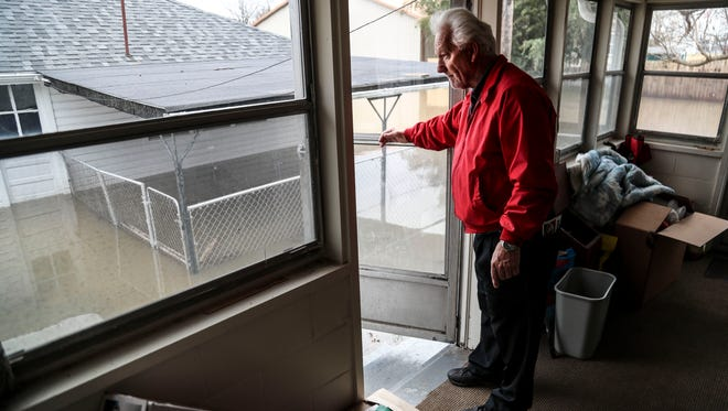 Perry Smith looks outside his back door to see the rising flood waters Sunday at his Utica home. He said he's hoping this year's flood wouldn't be as bad as the 1997 flood, which filled his home with three feet of water.