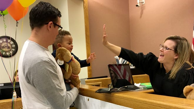 Paulie Russell, 1, with dad Chris Russell, gets a teddy bear and a high five from Livingston County Probate Court Judge Miriam A. Cavanaugh during the Michigan Adoption Day hearing Tuesday, Nov. 21, 2017, at 44th Circuit Court in Howell.