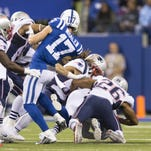 Colts wide receiver Griff Whalen (17) (left), looks to block Patriots defenders as teammate Colt Anderson is tackled during a bizarre and failed trick play during third quarter game action against New England.