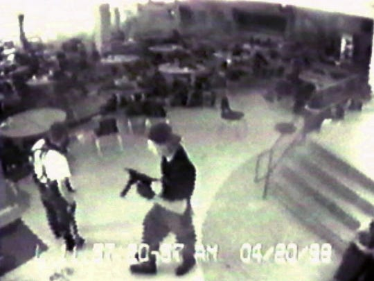 In this April 20, 1999, file photo, Eric Harris, left, and Dylan Klebold are seen carrying a TEC-9 semiautomatic pistol on a security camera image in the cafeteria at Columbine High School, in Littleton, Colo.