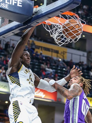 Indiana Pacers guard Victor Oladipo (4) slams a dunk despite defense from Sacramento Kings center Willie Cauley-Stein (00) during second quarter action between the Indiana Pacers and the Sacramento Kings at Banker's Life Fieldhouse, Indianapolis, Tuesday, Oct. 31, 2017.