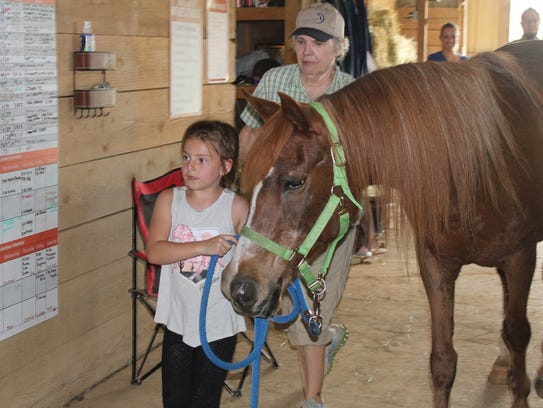 Six-year-old volunteer Katelynn West walks Mandy at Safe Harbor Equine and Livestock Sanctuary with Jackie Foster supervising her.