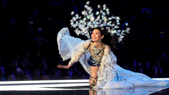 Ming Xi holds as smile as she falls on the runway.