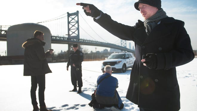 Camden County spokesman Dan Keashen, right, accompanies correspondents for the Norwegian newspaper Dagbladet as they photograph Camden County Police Lieutenant Richard Verticelli, background facing, on the Camden Waterfront for a story the newpaper in doing on the Camden County Police. 02.18.15