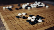 Black-and-white pieces occupy spaces on a board during a game of Go, which Google's software engineers say they've taught a computer program to play better than most humans.