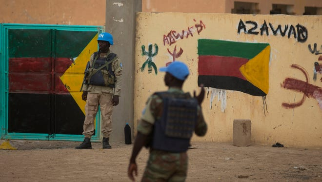 In this July, 27, 2013 photo, United Nations peacekeepers stand guard at the entrance to a polling station covered in separatist flags and graffiti supporting the creation of the independent state of Azawad, in Kidal, Mali.