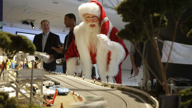 Brady White, as Santa Claus, plays with the Slot Mods USA Ultimate Slot Car Raceway during the unveiling of the Neiman Marcus Christmas Book, Tuesday, Oct. 7, 2014, in Dallas.