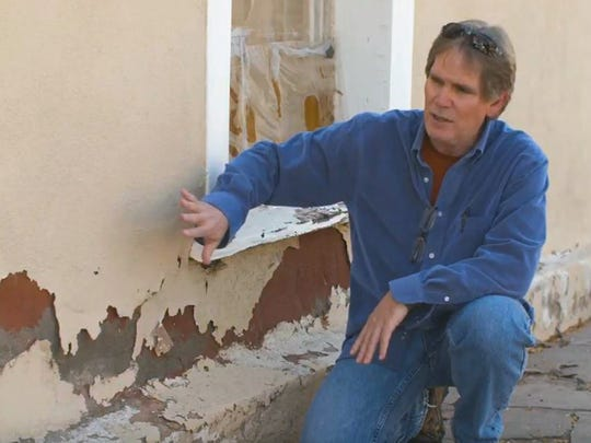 Eric Liefeld, president of Mesilla Valley Preservation, shows an adobe wall suffering deterioration after being painted with elastomeric material.