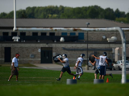At left, Bay Port defensive coordinator Al Schlies watches his players run drills during Friday's practice.