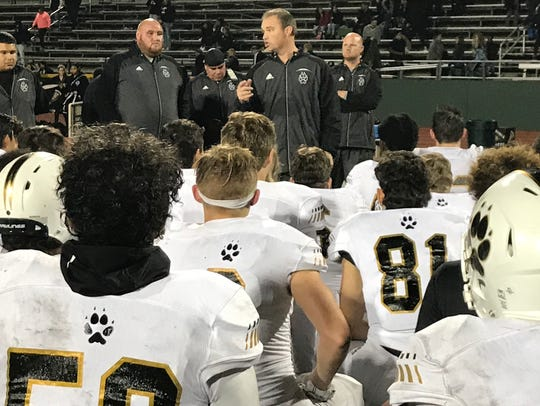 Head coach Casey Clausen speaks to his team after the
