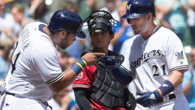 Jesus Aguilar (left) greets Brewers teammate Travis Shaw (21) at home plate after Shaw hit s three-run homer during the fifth inning of their game against the Arizona Diamondbacks Wednesday at Miller Park.