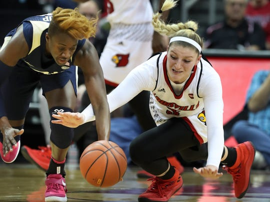 U of L's SamFuehring (3) battled Pittsburgh's Yacine Diop (12) for a loose ball at the Yum Center.    Feb. 25, 2018