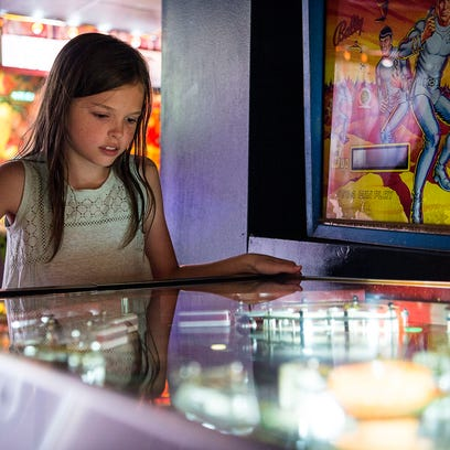 Ann Redman, 9, of Mars Hill, plays a the pinball game