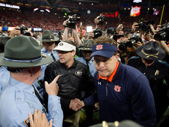 Auburn head coach Gus Malzahn, right, greets Georgia