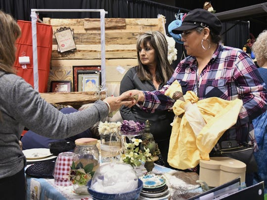 Michelle Parra speaks with customers during Visalia's community yard sale on Saturday, Jan. 6.