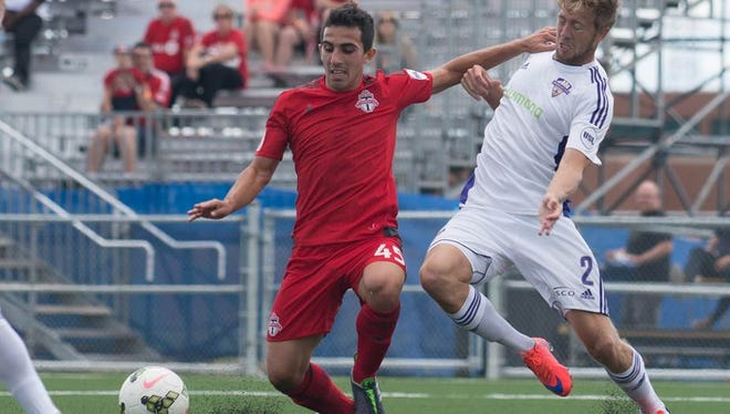 Louisville City FC's Bryan Burke fights for possession Saturday at Toronto.