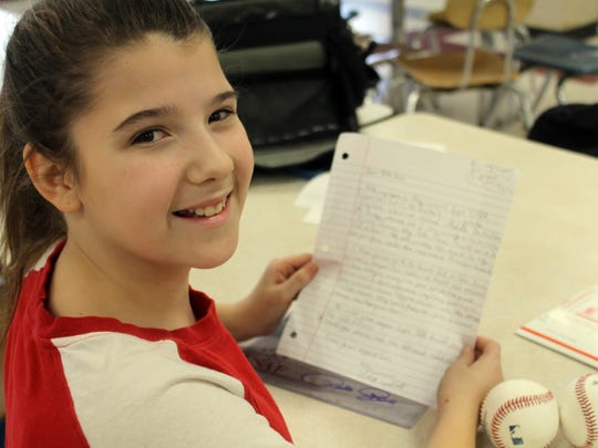Abby Campbell, 13, poses for a photo in Ashland, Ky. She holds a letter sent to her by Pete Rose.