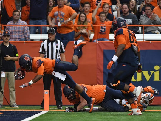 Syracuse running back Dontae Strickland (4) dives into