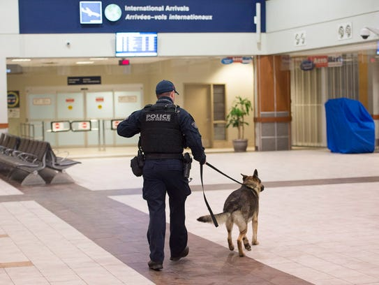 A police officer and a dog walk in the terminal at