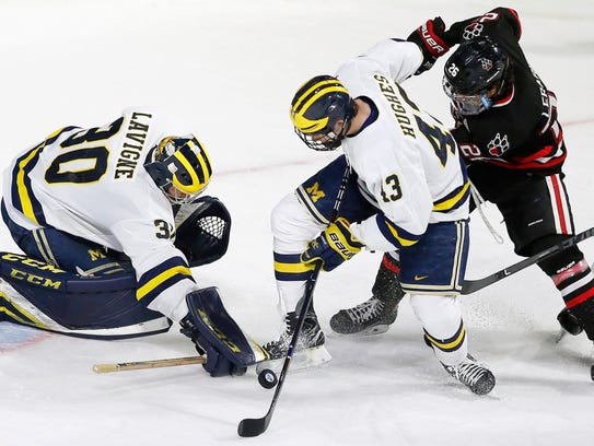 Michigan's Quinn Hughes, right, moves to clear the puck under pressure from Northeastern's Biagio Lerario in the NCAA tournament March 24, 2018.