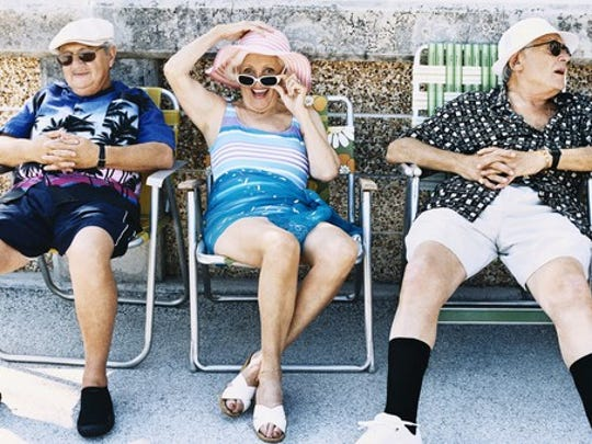 A group of seniors in lounge chairs smiling