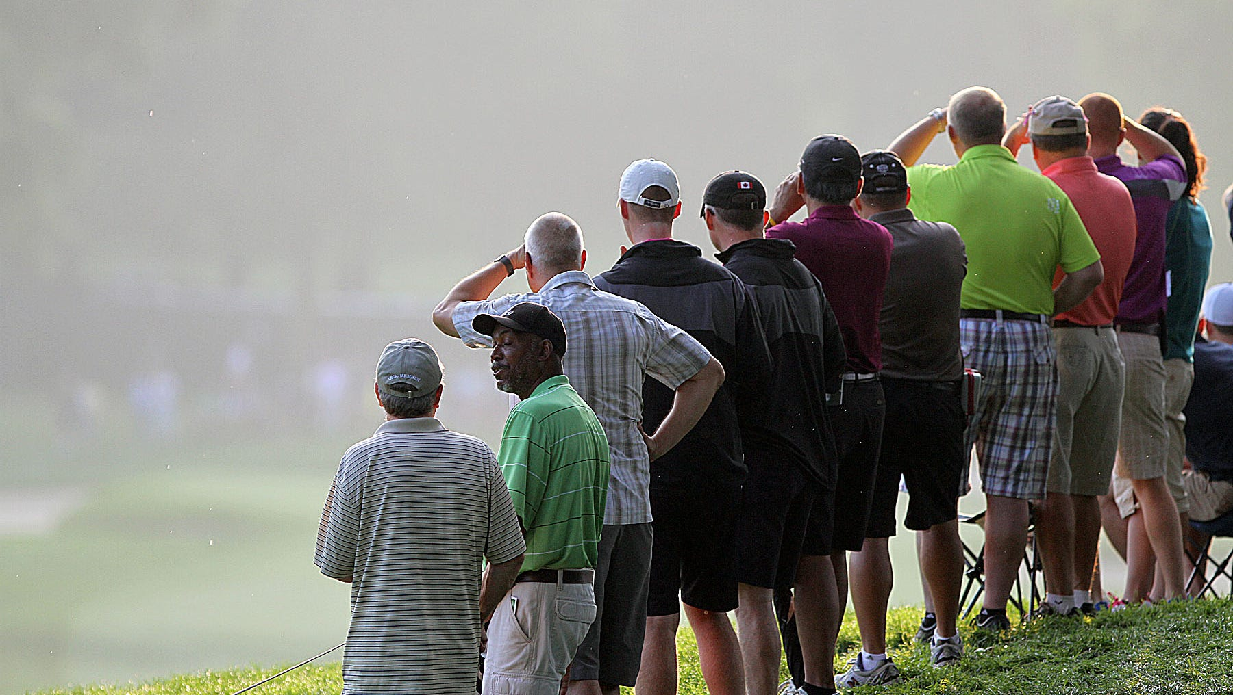 Spectators sheild their eyes from the sun as they watch the action thursday morning. Photo by Tina Yee