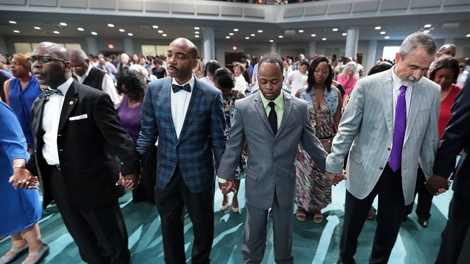 Brown Missionary Baptist Church pastor Bartholomew Orr (second from left) joins hands for a prayer during a 2016 service at the church's Swinnea Road campus. (Jim Weber/The Commercial Appeal)