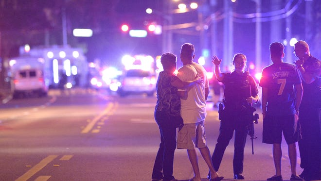 Orlando Police officers direct family members away from a multiple shooting at Pulse nightclub in Orlando, Fla., Sunday. A gunman opened fire, killing 50 and wounding 53 more, authorities said.