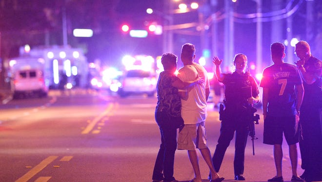 Orlando police officers direct family members away from a fatal shooting at Pulse Orlando nightclub in Orlando, Fla., Sunday, June 12, 2016.