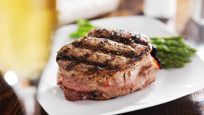 grilled steak filet with white wine and asparagus on wooden table with white wine