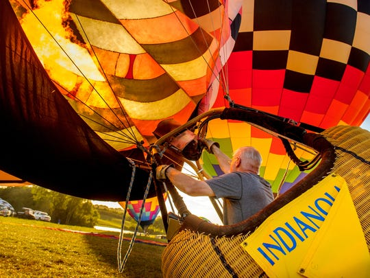 A balloonist sends a blast of heat and fire into his