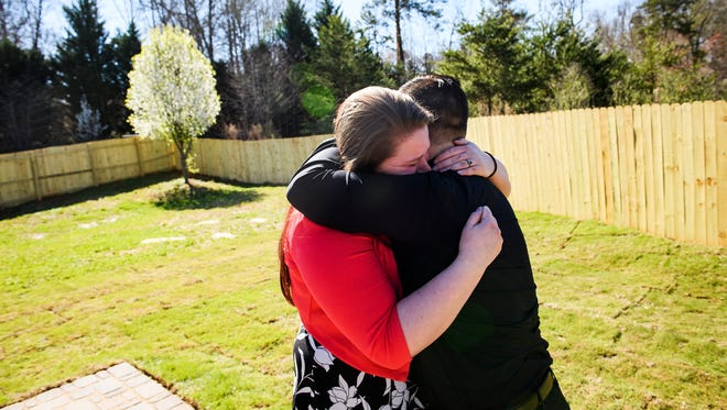 U.S. Army veteran Aaron Hillis and his wife Elizabeth embrace one another in the backyard of their new home in Boiling Springs on Friday, Mach 2, 2018. Hills received the home mortgage free from U.S. Bank, in conjunction with the Freedom Alliance. Hillis drove over an IED while on patrol with his squad in Afghanistan in 2012. He was medically-retired in 2017 and was awarded a Purple Heart for the injuries he sustained during the incident.
