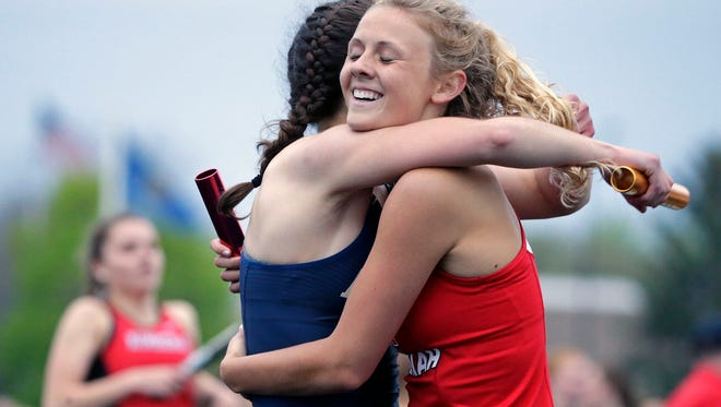 Sydney Squier, left of Appleton North and Krista Baumgartner of Neenah hug following the 4x400 Meter Relay as the Fox Valley Association track and field conference championships take place Monday, May 14, 2018, in Kimberly, Wis.